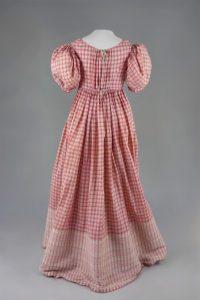 Empirekleid mit rot-weißen Karos. Um 1815. Baumwolle, gewebt.