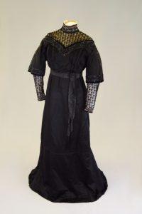 Schwarzes Belle Époque-Kleid. Um 1900. Seidenatlas, Tüllspitze, Pailletten.